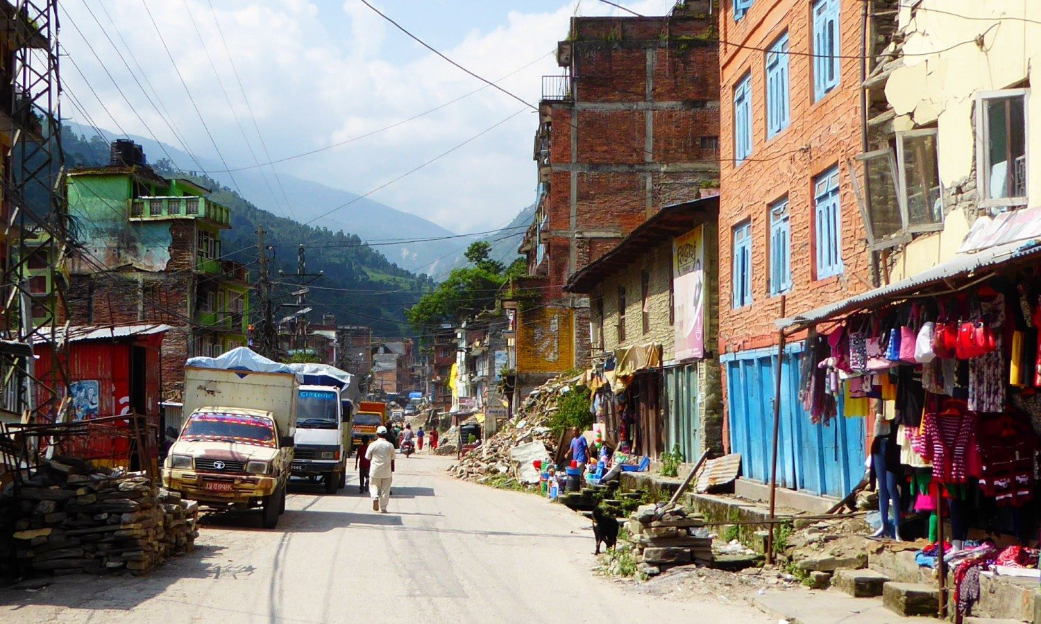 The main road in Bahrabise, Sindhupalchowk, four months after the earthquake. Piles of rubble and building materials line the road.
