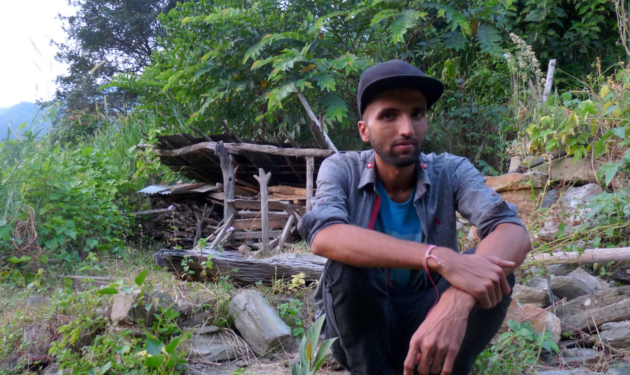 Ram Sharan Parajuli next to his old house.