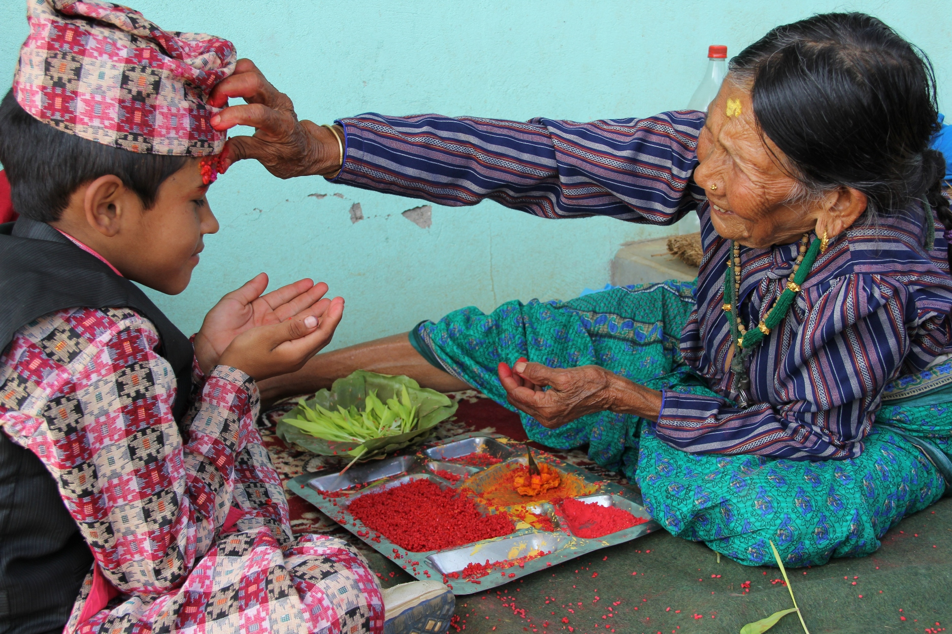 "His mother, Bhagbati Thapa, as matriarch of the family, receives kinfolk from far and wide to bestow tika, a significant blessing of good fortune for the coming year. ""This is an important tika for us,"" added Krishna. ""We have to hope for the future."" Their house may be irreparably damaged, but it was still put to good use by the thirty friends and relatives who congregated outside in its shade to eat, chat and play games. For this Dashain, as in previous years, the hills of Gorkha resound with drumming, singing and laughter well into the early hours."