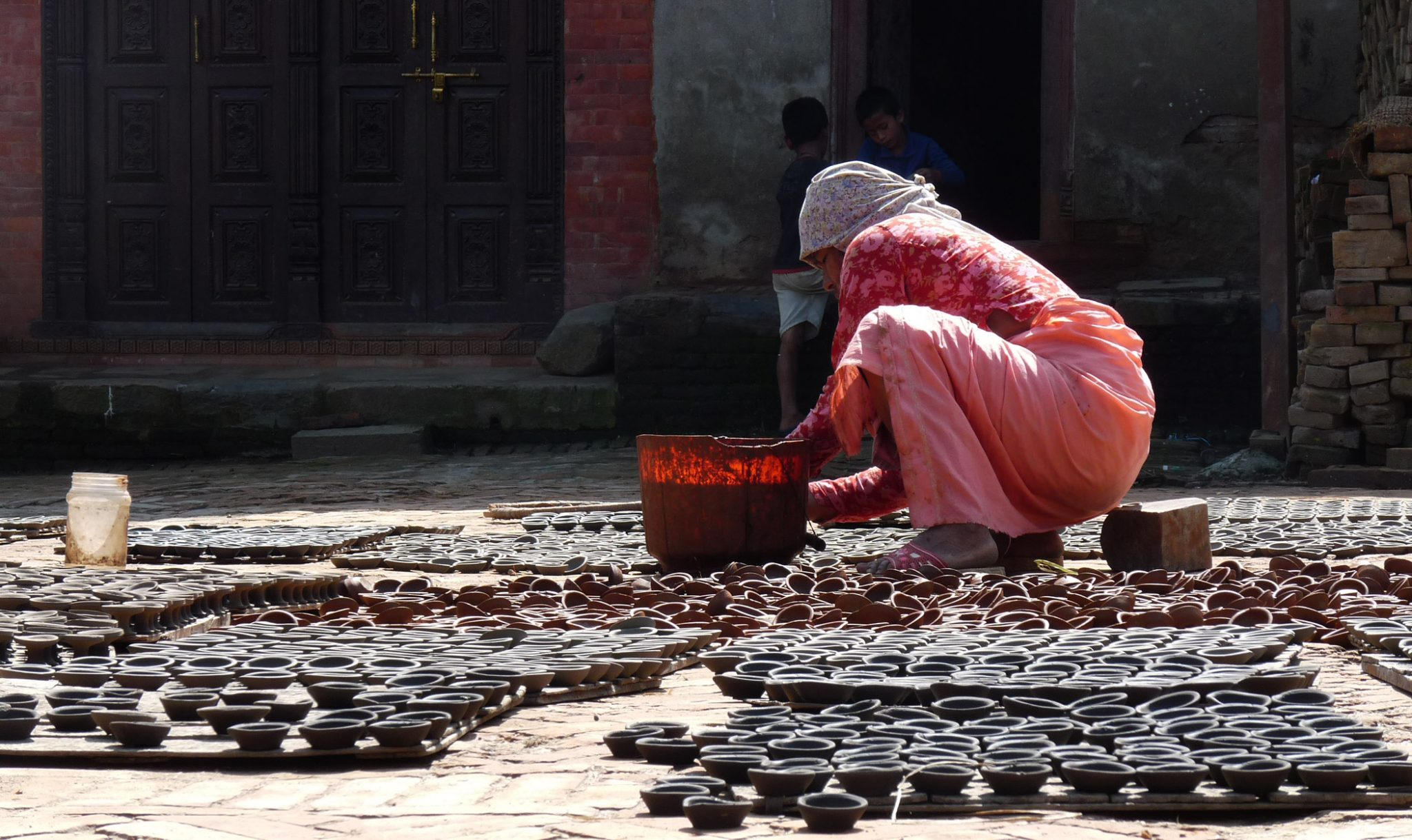 "Bhaktapur is famous for its traditional pottery industry, and is home to two ""pottery squares"" where rows of clay pots can be seen drying in the sun. The potters are particularly busy during the Tihar festival of lights - one of the biggest festivals in Nepal - making diyekos (earthen lamps) which are then filled with oil and lit outside each household. In Hinduism, fire is an important symbol of cleansing and purification and its light dispels gloom and darkness."