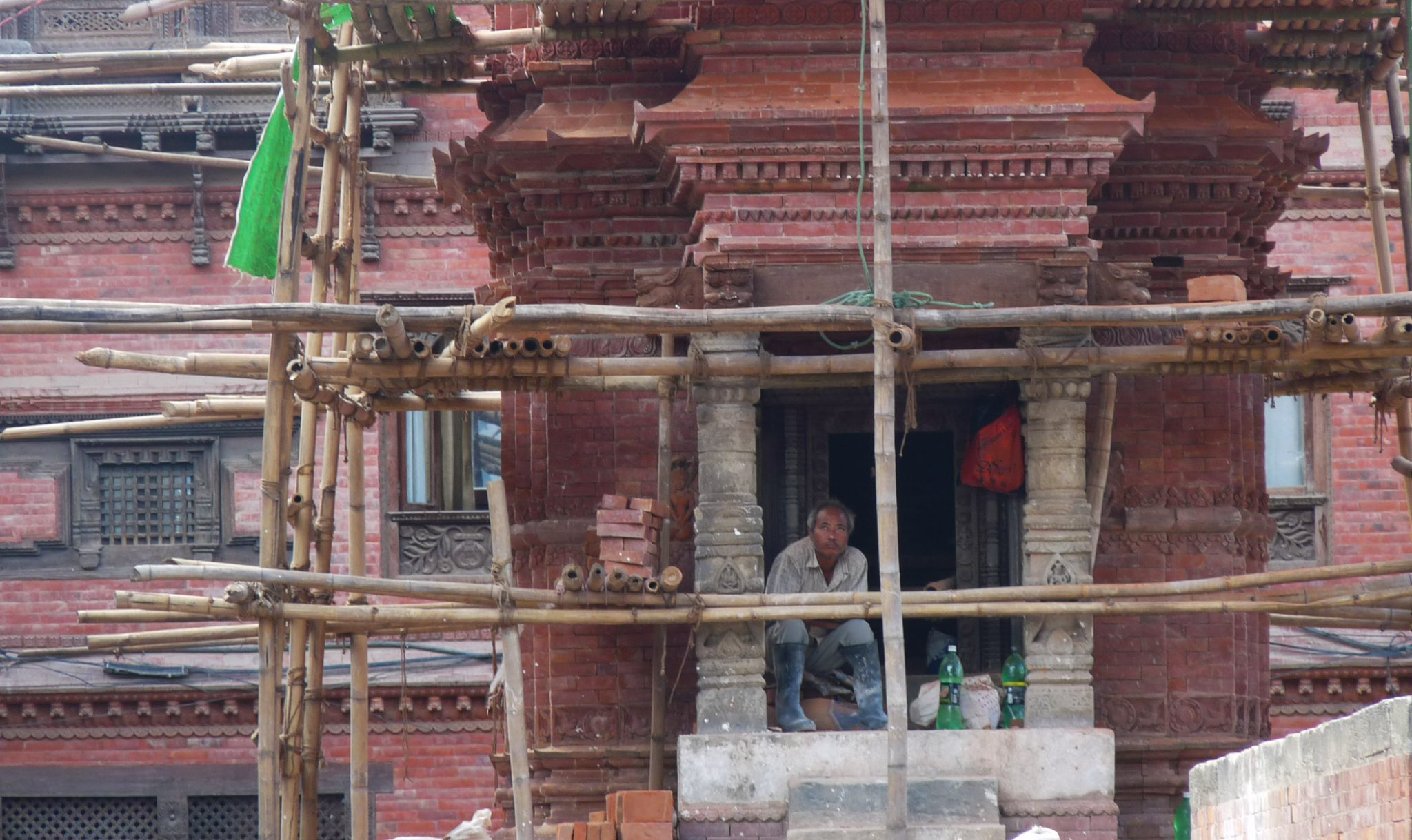 A man sits in the damaged entrance to a temple.