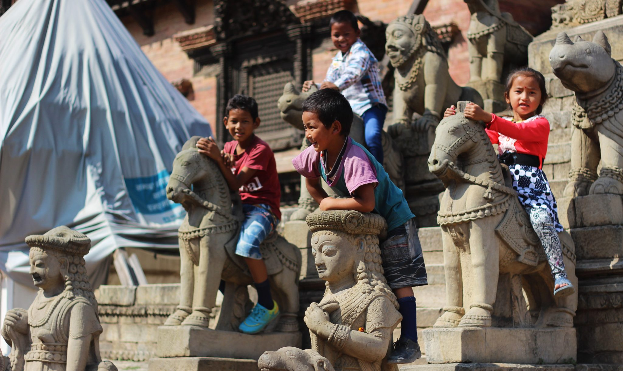 Children play on the stone animals guarding the entrance to the Siddhi Laxmi temple, a 17th-century temple which escaped relatively unscathed from the earthquake.